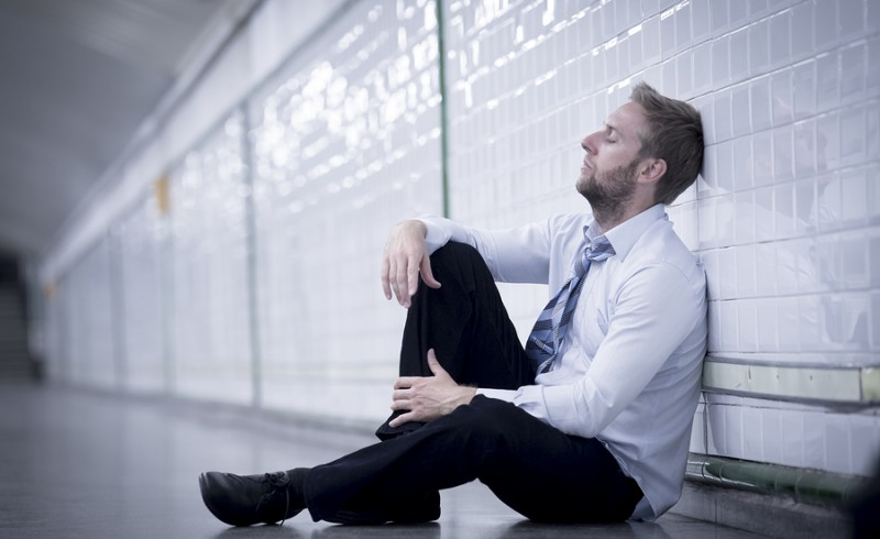 Young Businessman Lost In Depression Sitting On Ground Street Su