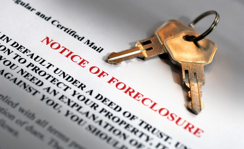 House keys and foreclosure notice in dramatic light
