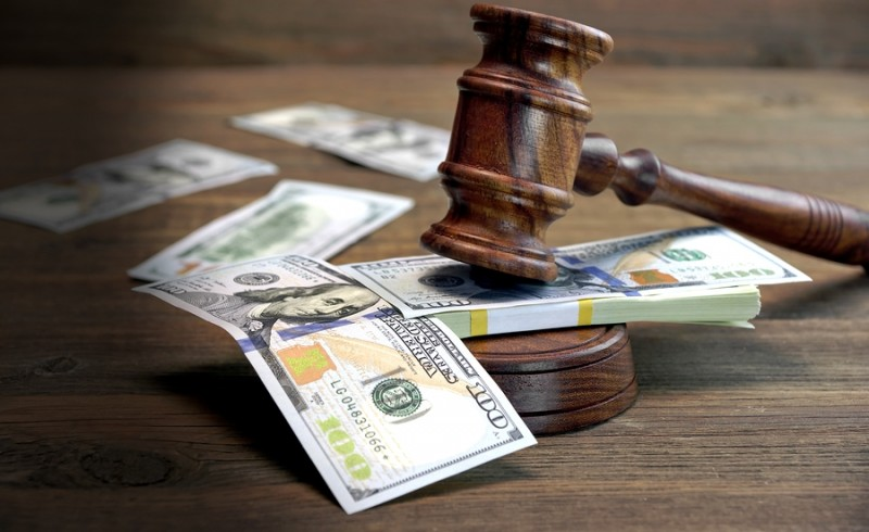Concept For Corruption Bankruptcy Court Bail Crime Bribing Fraud Auction Bidding. Judges or Auctioneer Gavel Soundboard And Bundle Of Dollar Cash On The Rough Wooden Textured Table Background.
